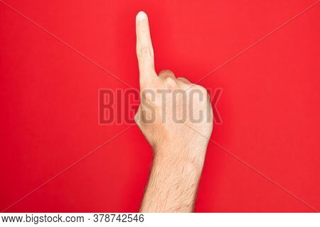 Hand of caucasian young man showing fingers over isolated red background counting number one using index finger, showing idea and understanding