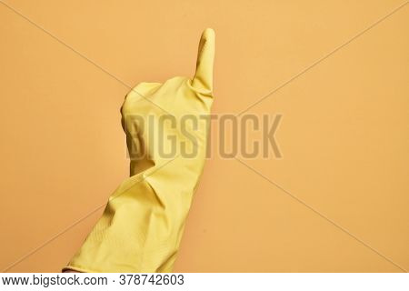 Hand of caucasian young man with cleaning glove over isolated yellow background showing little finger as pinky promise commitment, number one