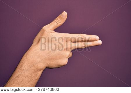 Hand of caucasian young man showing fingers over isolated purple background gesturing fire gun weapon with fingers, aiming shoot symbol