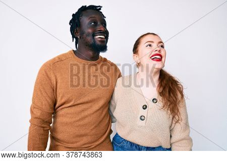 Interracial couple wearing casual clothes looking away to side with smile on face, natural expression. laughing confident.