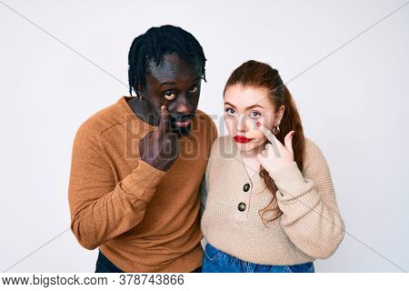 Interracial couple wearing casual clothes pointing to the eye watching you gesture, suspicious expression