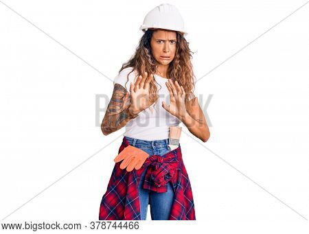 Young hispanic woman with tattoo wearing hardhat and builder clothes disgusted expression, displeased and fearful doing disgust face because aversion reaction. with hands raised