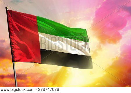 Fluttering United Arab Emirates Flag On Beautiful Colorful Sunset Or Sunrise Background. United Arab