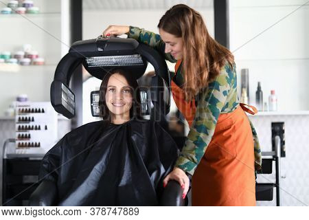 Happy Hairdresser Sets Up Equipment For Drying Hair. A Completed Haircut Emphasizes Strengths And Hi