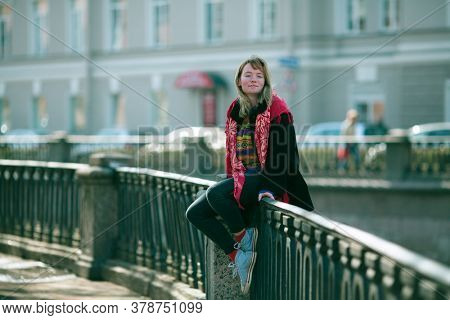 A young girl sits on the railing of the river embankment in Saint Petersburg.