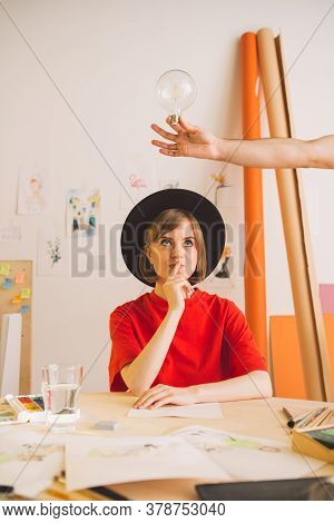 Young Pretty Girl Artist In Hat Thinks And Idea Comes In Studio. Insight Is Symbolized By A Light Bu
