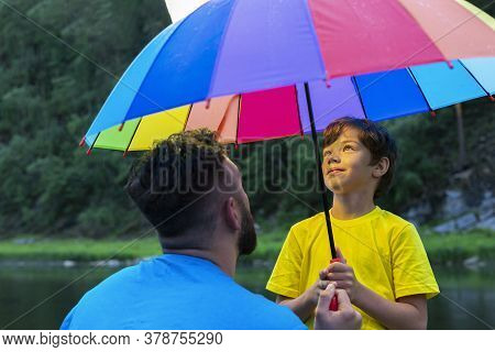 Bearded Man And His Teen Sun Under Umbrella Look Up. Boys Face Lit