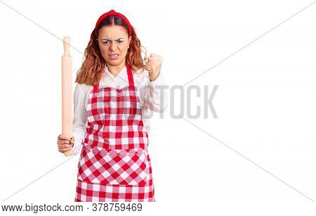 Young latin woman wearing apron holding kneader annoyed and frustrated shouting with anger, yelling crazy with anger and hand raised