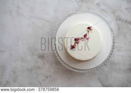 Small Ousse Cake With Smooth White Glaze Decorated With Dried Rose Buds  In Concise Simple Design On