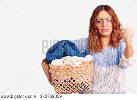 Young latin woman holding laundry basket annoyed and frustrated shouting with anger, yelling crazy with anger and hand raised