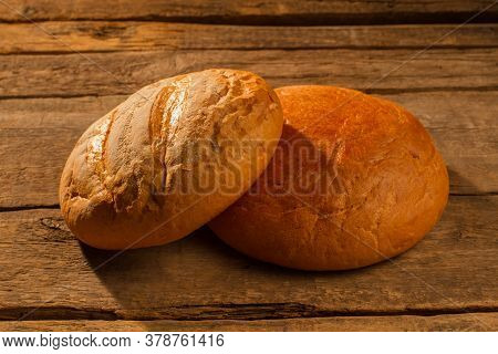 Two Round Loaves Of Homemade Bread. Crusty Bread On Wooden Background.
