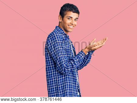 Young african amercian man wearing casual clothes pointing aside with hands open palms showing copy space, presenting advertisement smiling excited happy