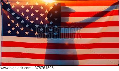 Woman Silhouette In The Agricultural Field Beyond The American Flag On Sunset