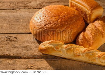 Assorted Artisan Bread On Wooden Background. Freshly Baked Bread With Golden Crust.