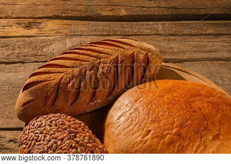 Fresh Crusty Bread On Wooden Background. Artisan Bread Loaves. Delicious Homemade Pastry.
