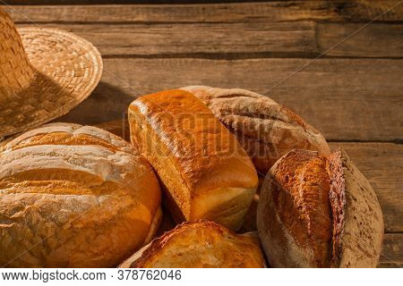 Various Types Of Organic Bread On Wooden Background. Artisan Bread Background. Copy Space.