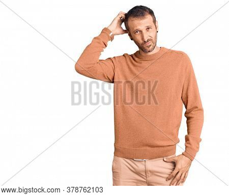 Young handsome man wearing casual clothes confuse and wonder about question. uncertain with doubt, thinking with hand on head. pensive concept.