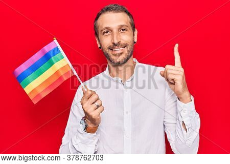 Young handsome man holding rainbow lgbtq flag smiling with an idea or question pointing finger with happy face, number one