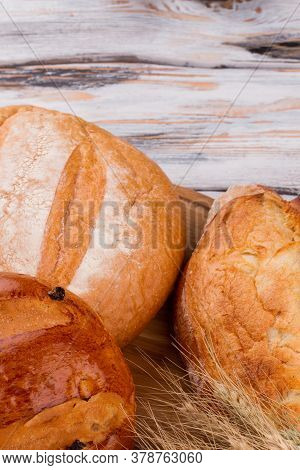Freshly Baked Bread With Wheat Ears. Artisan Bread On Wooden Background, Top View.