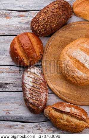 Top View Of Various Bakery Products On Wooden Background. Freshly Baked Artisan Bread On Wood Boards