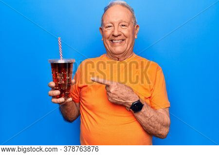 Senior handsome grey-haired man drinking cola refreshment beverage over blue background smiling happy pointing with hand and finger