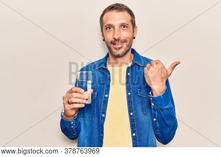 Young handsome man drinking glass of water pointing thumb up to the side smiling happy with open mouth