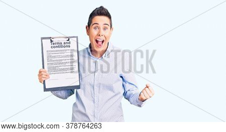Young woman with short hair holding clipboard with terms and conditions document screaming proud, celebrating victory and success very excited with raised arms