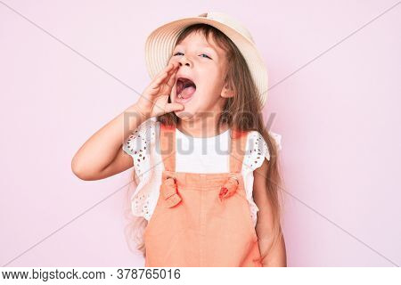 Little caucasian kid girl with long hair wearing spring hat shouting and screaming loud to side with hand on mouth. communication concept.