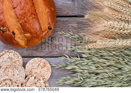 Bread And Wheat Ears On Wooden Background. Wheat, Oat Ears And Healthy Dietary Bread On Old Wooden T