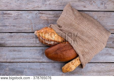 Artisan Bread In Burlap Bag, Top View. Freshly Baked Homemade Bread On Wooden Background. How To Sto