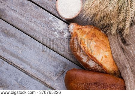 Bread With Wheat Ears And Bowl Of Flour. Homemade Bread With Wheat Ears And Flour On Rustic Wooden B