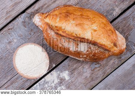 Fresh Artisan Bread And Bowl With Flour. Delicious Homemade Bread On Old Wooden Background.