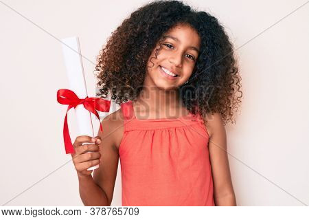 African american child with curly hair holding graduate degree diploma looking positive and happy standing and smiling with a confident smile showing teeth