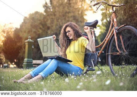 young woman in a park rejoices happy in front of a computer