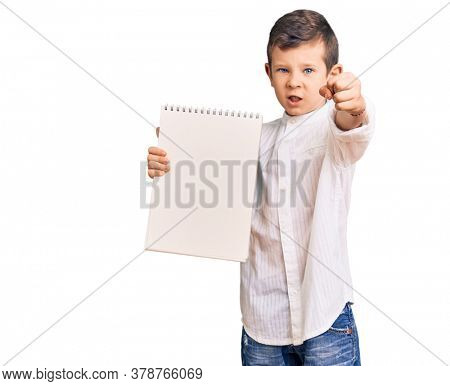 Cute blond kid holding notebook annoyed and frustrated shouting with anger, yelling crazy with anger and hand raised