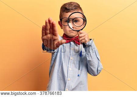 Cute blond kid wearing nerd bow tie and glasses holding magnifying glass with open hand doing stop sign with serious and confident expression, defense gesture