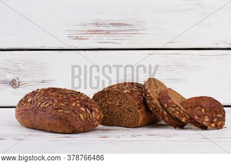 Wholemeal Bread On Wooden Background. Fresh Rye Bread Cutting Into Slices. Space For Text.