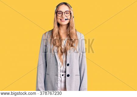Young beautiful blonde woman wearing call center agent headset with a happy and cool smile on face. lucky person.