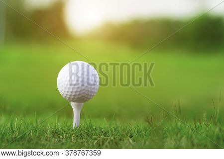 Golf Ball On Tee In A Beautiful Golf Course With Morning Sunshine.ready For Golf In The First Short.