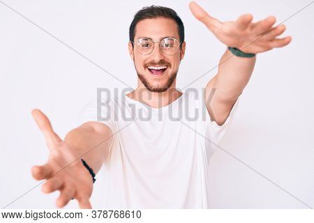 Young handsome man wearing casual clothes and glasses looking at the camera smiling with open arms for hug. cheerful expression embracing happiness.