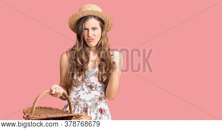 Beautiful caucasian young woman wearing summer hat and holding picnic wicker basket with bread annoyed and frustrated shouting with anger, yelling crazy with anger and hand raised
