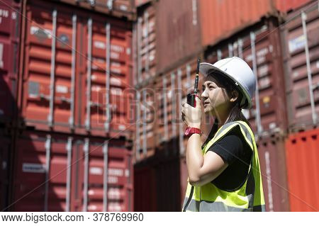 Young Asian Woman In Safety Uniform Hand Taking Walkie Talkie At The Container Depot.