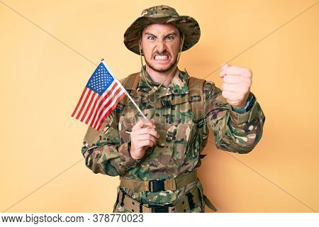 Young caucasian man wearing camouflage army uniform holding usa flag annoyed and frustrated shouting with anger, yelling crazy with anger and hand raised