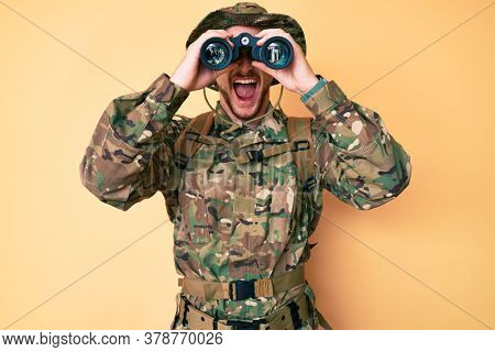 Young caucasian man wearing camouflage army uniform using binoculars smiling and laughing hard out loud because funny crazy joke.