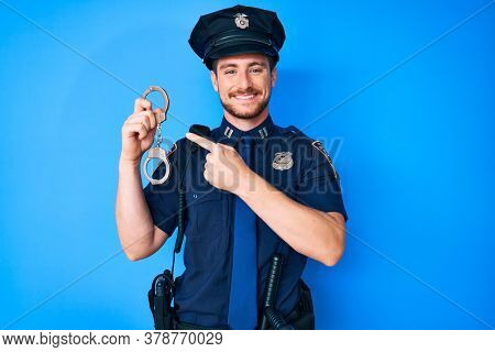 Young caucasian man wearing police uniform holding handcuffs smiling happy pointing with hand and finger