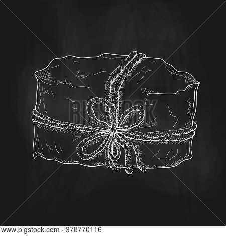 Chalk Drawn Gift Illustration On Black Chalkboard. Craft Paper Wrapped Package Tied With Cord Or Twi
