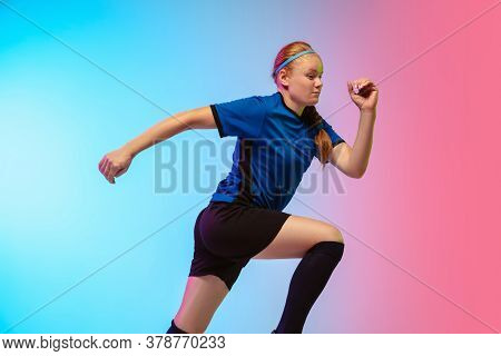On The Run. Female Soccer, Football Player Training In Action Isolated On Gradient Studio Background