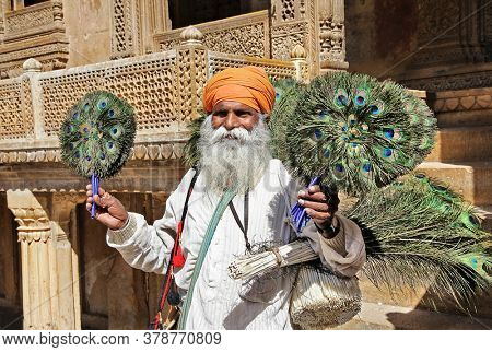 Jaisalmer old city, daily life of indian people.  old man selling peacock feathers. Feb 2013 Rajastan, India