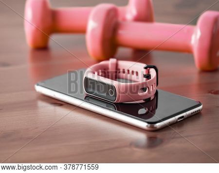 Fitness Tracker On Smartphone And Pink Colored Dumb-bell On Wooden Tabletop. Pink Female Pedometer O