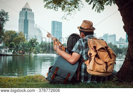 Young Couples Sit And Watch The Cityscape. In A Romantic And Happy. At Public Park During The Travel